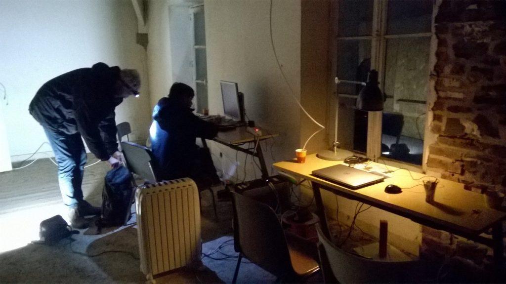 Photo de deux personnes dans la pénombre d'un grenier, l'un devant un écran l'autre avec une lampe frontale
